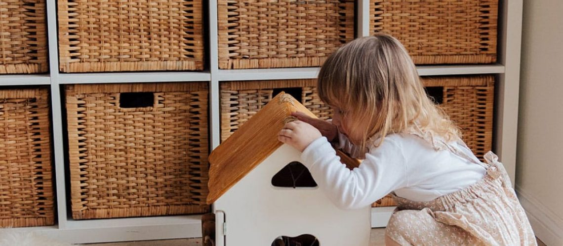 girl-playing-with-a-wooden-toy-house-3933028